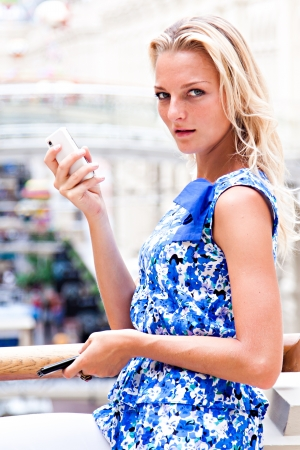 Young and beautiful woman with blond hair is on the phone at the mall Stock Photo - 15896216