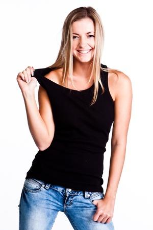 playera negra: Joven, bella y feliz con una camisa negro y blue jeans Foto de archivo