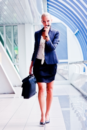 Business woman with a briefcase comes to the business center photo