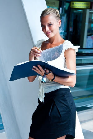 young and beautiful business woman exploring documents in a blue folder