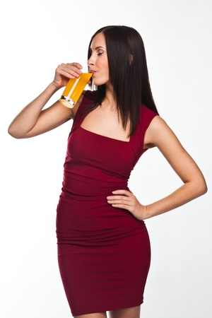 beautiful young woman in a red evening gown with a glass of juice photo