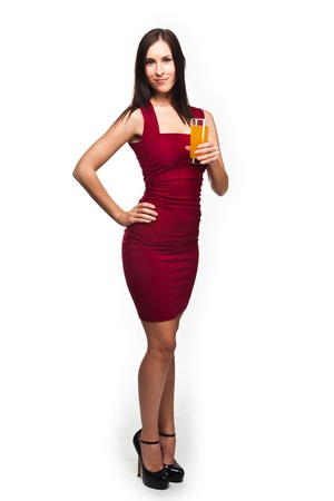 red evening: beautiful young woman in a red evening gown with a glass of juice