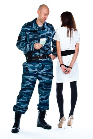 A police officer arrests a young woman photo