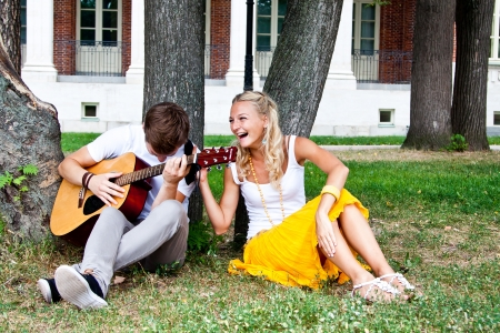 A young man plays guitar in the park beautiful woman photo