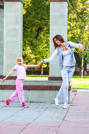 young mother walking in the park with a beautiful daughter photo