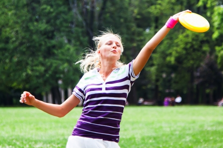 young and beautiful woman playing frisbee in the park Stock Photo