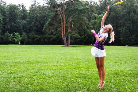 young and beautiful woman playing frisbee in the park photo