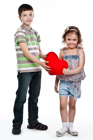 little boy gives a girl a plush heart  photo