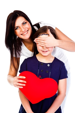 young and beautiful mother gives her daughter a heart photo