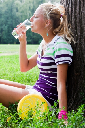 young and beautiful woman drinks water in park photo