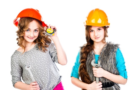Two young beautiful girls in building helmet and tools in hand Stock Photo - 18054179