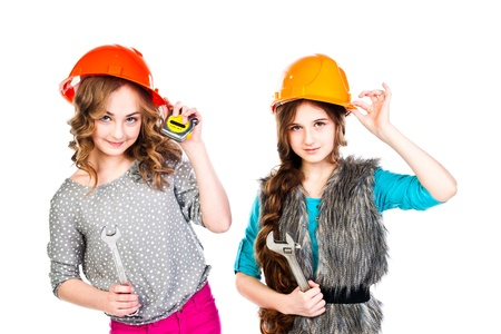 Two young beautiful girls in building helmet and tools in hand Stock Photo - 18053873