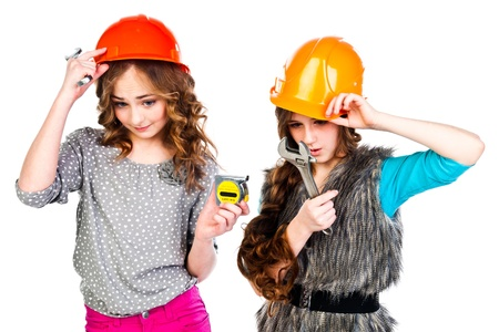 Two young beautiful girls in building helmet and tools in hand Stock Photo - 18053885