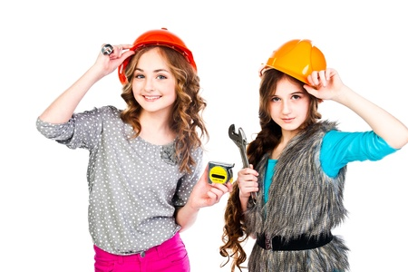 Two young beautiful girls in building helmet and tools in hand Stock Photo - 18053882