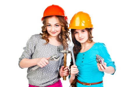 Two young beautiful girls in building helmet and tools in hand Stock Photo - 18054074