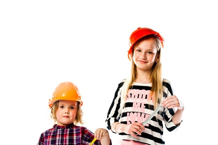 Two young beautiful girls in building helmet and tools in hand Stock Photo - 18054321