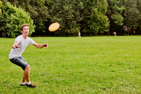 young and handsome man playing frisbee