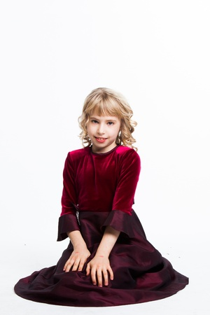 small and beautiful girl in a red dress photo