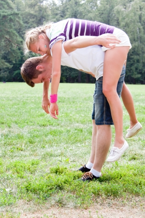man holding woman on his back during a walk in the park photo