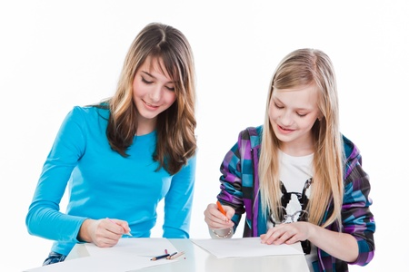 two beautiful girls draw with pencils photo