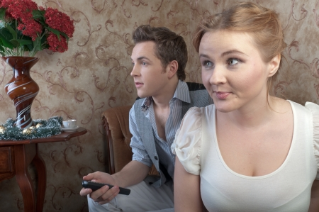 a pair of young beautiful people watching television photo