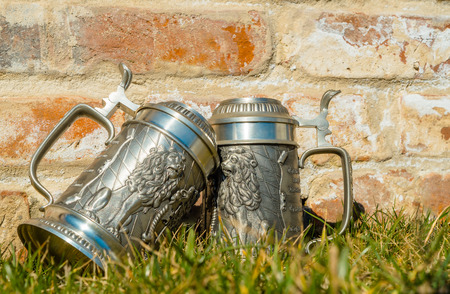 near beer: two vintage beer mugs on the green grass near the old red brick wall Stock Photo