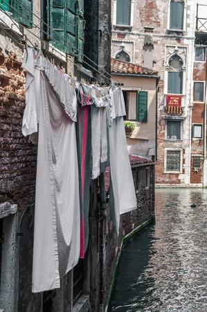wet clothes: ropa mojada colgando de una cuerda sobre el agua en Venecia