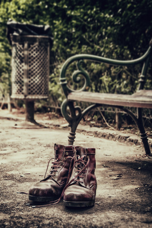 tough times: lost old shoes on the ground in the park