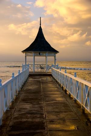 Zicht op Zonsondergang in Gazebo en de pier op het strand van Half Moon Resort, Rose Hall, Jamaica