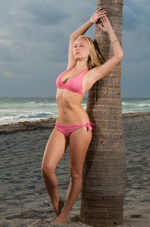 A young caucasian women relaxes in the beach in a stormy morning. photo
