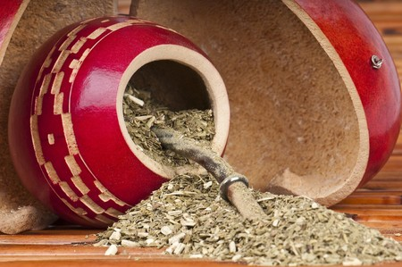 Close up of calabash cup with spill of yerba mate tea and straw. Use of Selective Focus. photo
