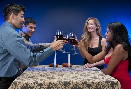 Group of mixed races friends toasting in night club or restaurant. photo