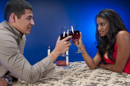 Latin couple drinking wine and toasting in a night club or restaurant setting. photo