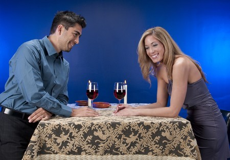 Couple drinking wine and having fun in night club or restaurant setting. Male model young in his 20s with mature woman in her 40s. photo