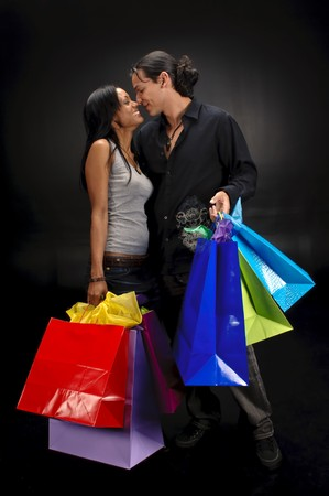 Happy couple with shopping bags in a black background. photo