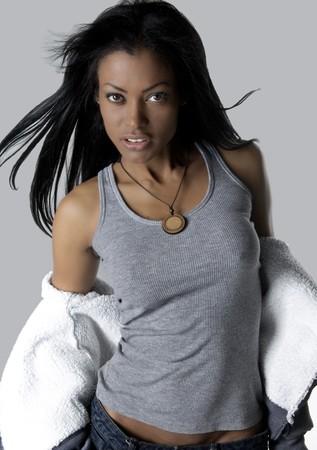 Hispanic model staand zeer sensual op een grijze achtergrond.