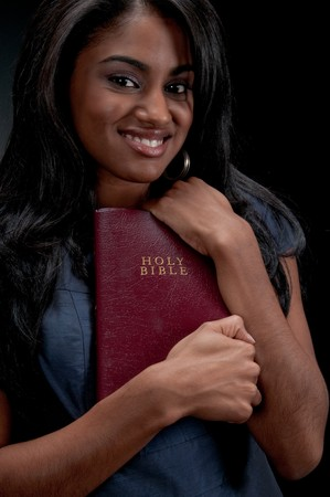 Portrait of young hispanic woman holding bible in black background. Stock Photo - 4407913