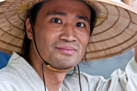conical: Portrait of young oriental male with typical hat. Stock Photo