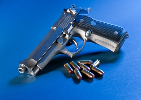 45 caliber: Close up view of bullets and automatic gun.
