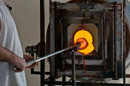 Glass artisan works with hot glass to create an artistic piece. Stock Photo - 4542302
