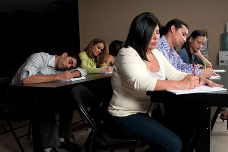 Student falling asleep during a night class training in a corporate classroom. Stock Photo