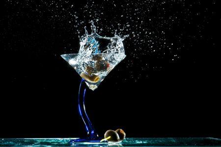 Splash van olijven in een martini glas. Stockfoto