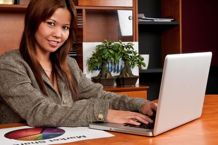 Young worker in an small office enviroment setting working in laptop. Stock Photo - 4768033