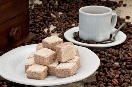 Coffee beans and wafer cookies with cup and grinder. photo