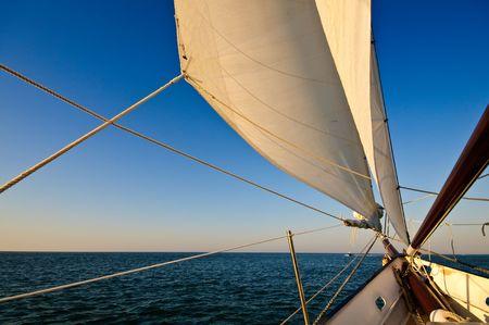 deportes nauticos: Velero navegando hacia la puesta de sol en el Caribe. Foto de archivo