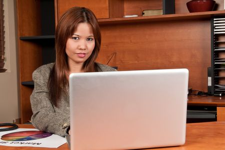Young woman very happy working in a laptop in small office. Stock Photo - 4828011