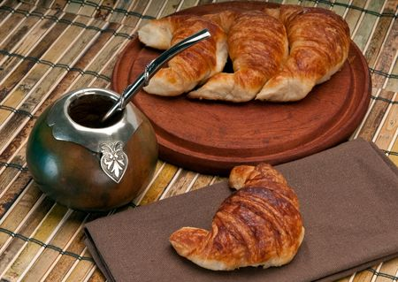 Cup of calabash and Croissants, this is a typical drink and breakfast in Argentine. Use of selective focus. photo