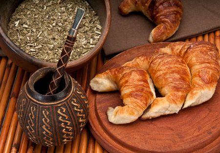 yerba mate: Taza de calabaza de mate y medialunas, con yerba mate en el primer plano. Mate es una tradici�n muy popular en Argentina y Uruguay.