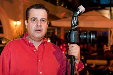 Photographer covering an event at night in a restaurant. Outdoor setting. photo