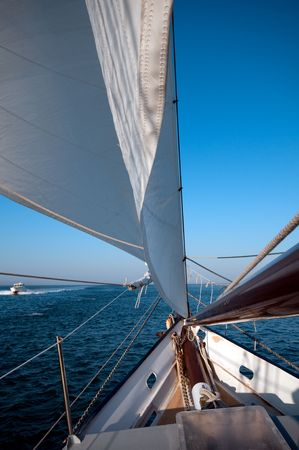 Sailboat navigates in the ocean while a boat is passing by. Stock Photo